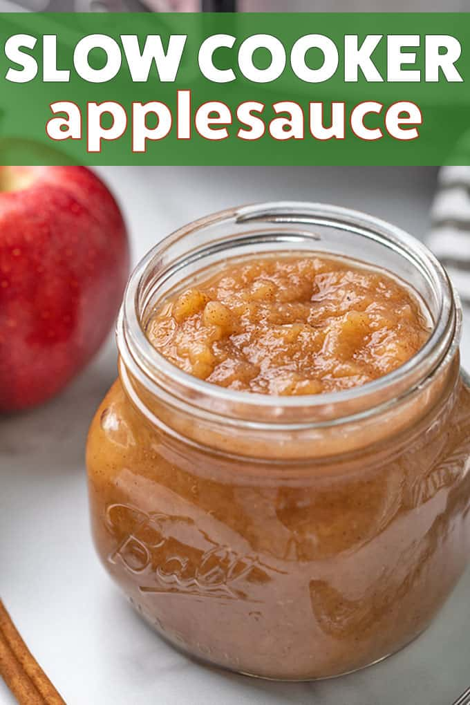 Applesauce in a small jar beside a red apple.