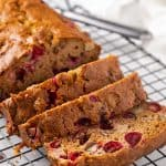 Sliced cranberry apple bread on a black wire cooling rack