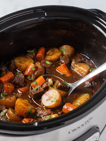 Balsamic beef stew in an oval slow cooker with a ladle