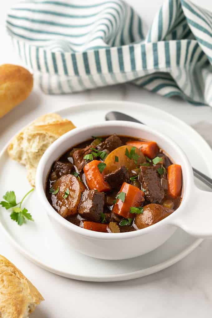Balsamic beef stew in a white bowl on a white plate with a spoon.