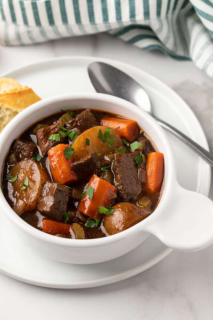 Balsamic beef stew in a white bowl on a white plate with a spoon and bread.