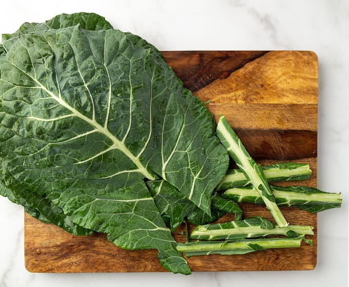 Collard leaves with stems cut and removed on a cutting board