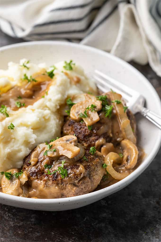 Hamburger steak with gravy and mashed potatoes in a white bowl with a fork