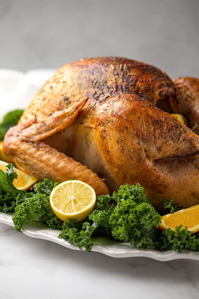 A roasted turkey on a white platter garnished with kale and fruit