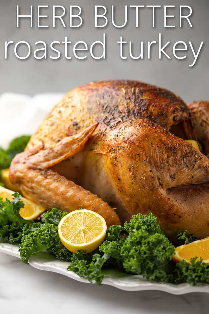 A roasted turkey on a white platter garnished with kale, lemons and oranges.