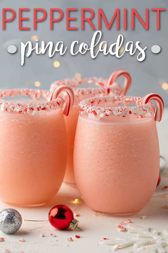 Three glasses of pink frozen cocktails garnished with candy canes.