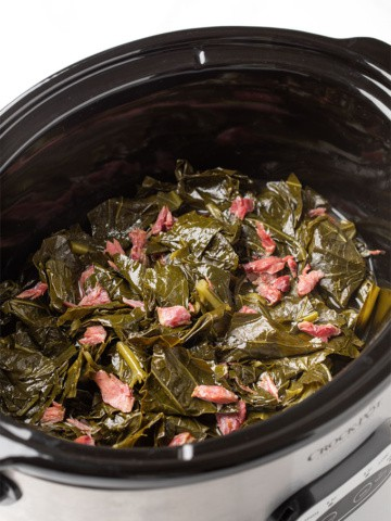 Collards and ham hocks in an oval slow cooker