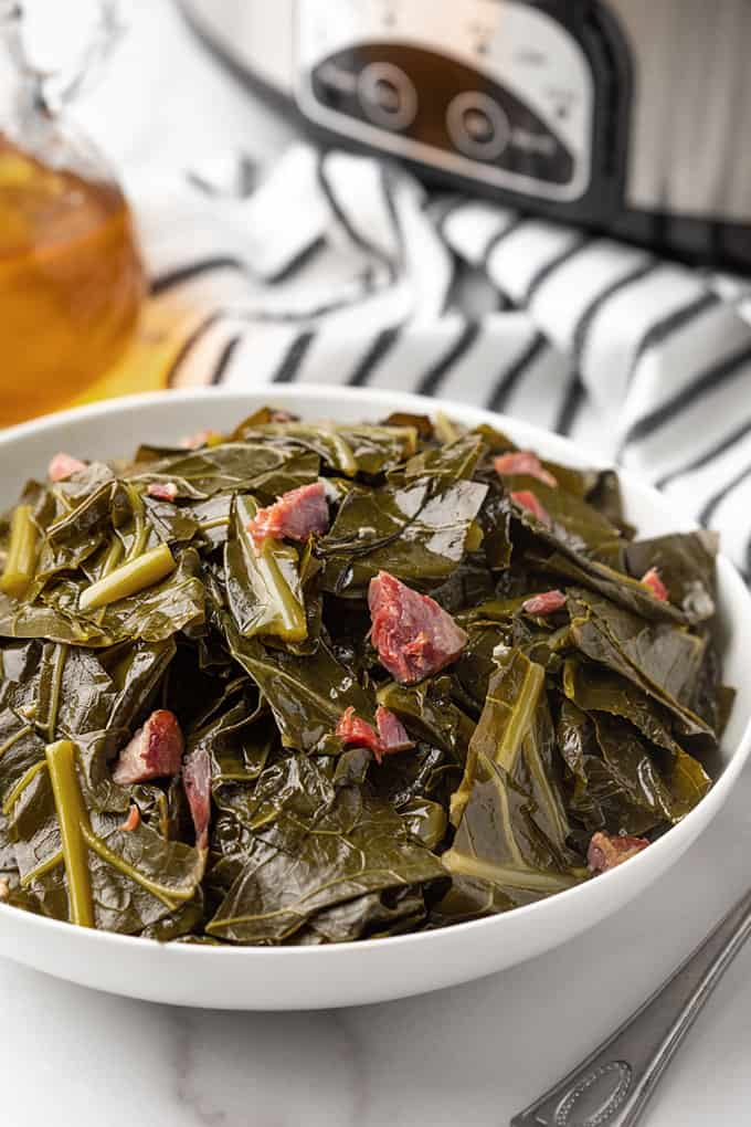 Collard greens in a white bowl with a slow cooker in the background