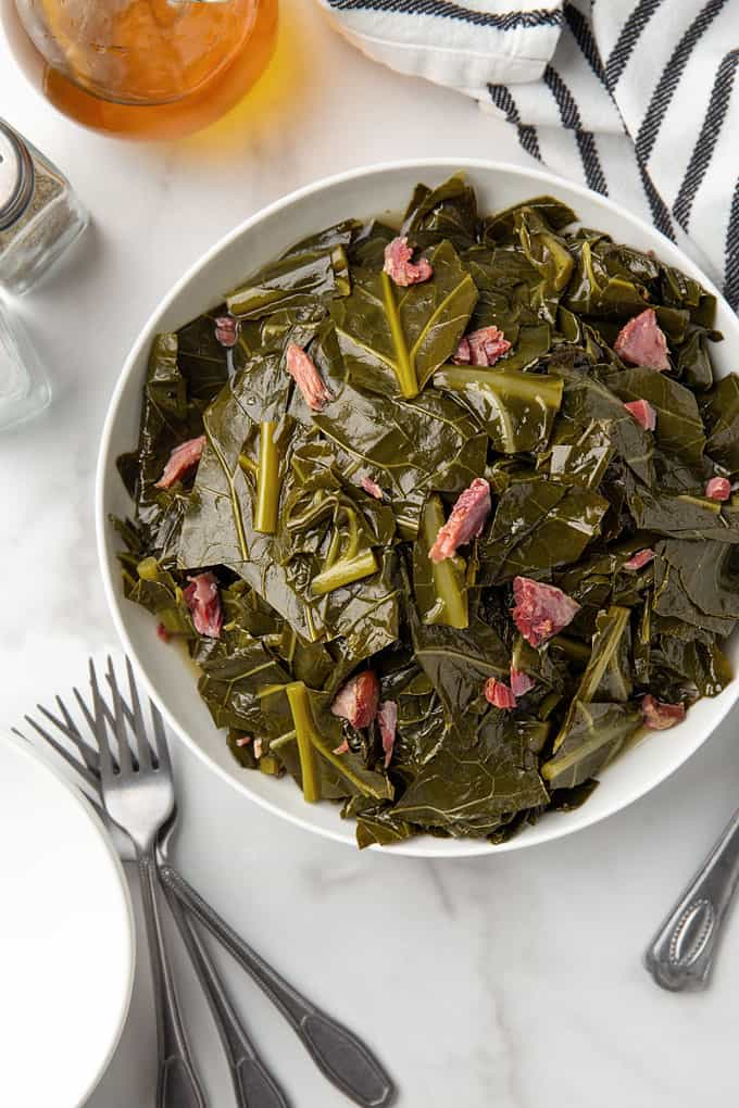 Slow cooked collard greens and ham hocks in a white bowl