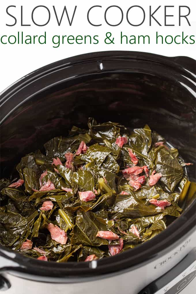 Cooked collards with pieces of ham hocks in an oval slow cooker.