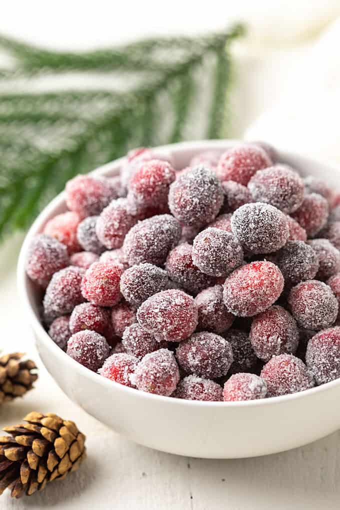 Sugared cranberries in a white bowl beside 2 mini pine cones