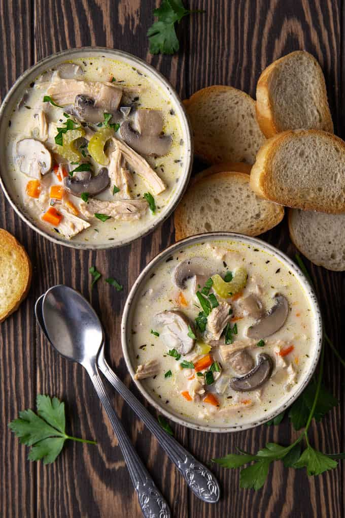 Overhead view of 2 bowls of creamy turkey and mushroom soup beside slices of French bread