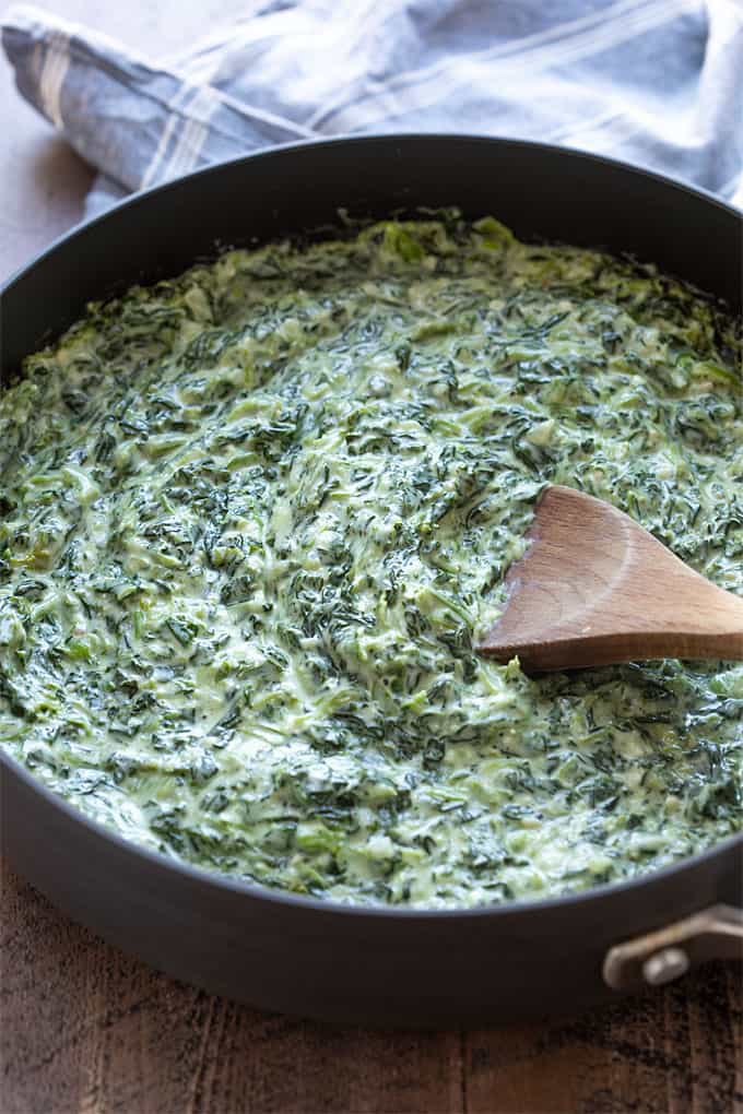 Creamed spinach in a large skillet with a wooden spoon