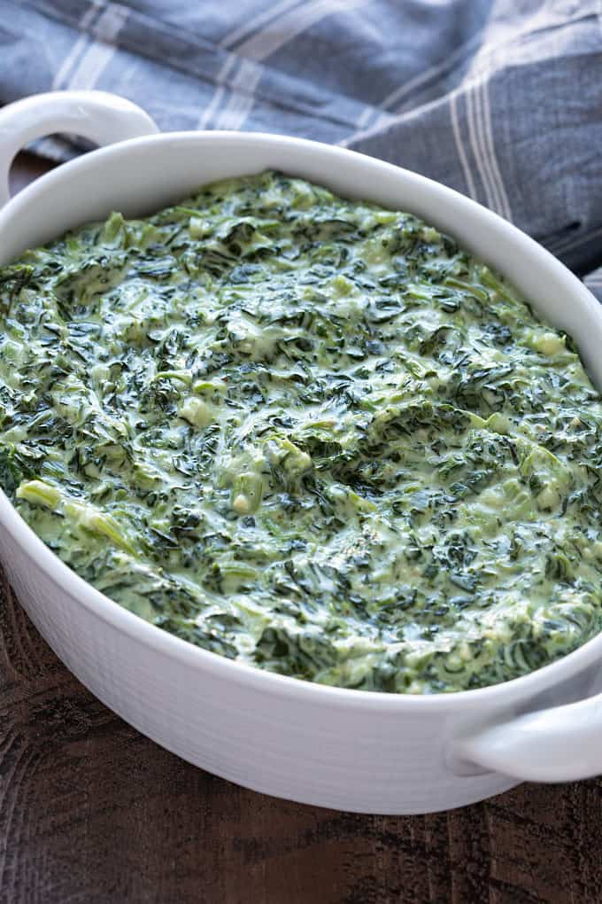 Creamed spinach in an oval white serving dish beside a denim cloth napkin.
