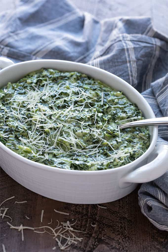 Creamed spinach topped with grated Parmesan in an oval white serving dish with a serving spoon