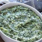 Creamed spinach in a white baking dish with a spoon. Overlay text at top of image.