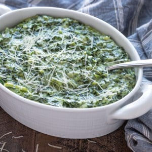 Creamed spinach in a white oval baking dish with a serving spoon.