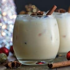 White russian cocktail prepared with eggnog and garnished with star anise and a cinnamon stick