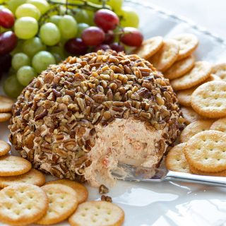 A shrimp cheese ball on a platter with a cheese spreader, crackers and grapes