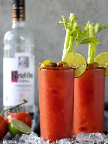 Two bloody mary cocktails with garnishes. A bottle of vodka, tomatoes and a lime is in the background