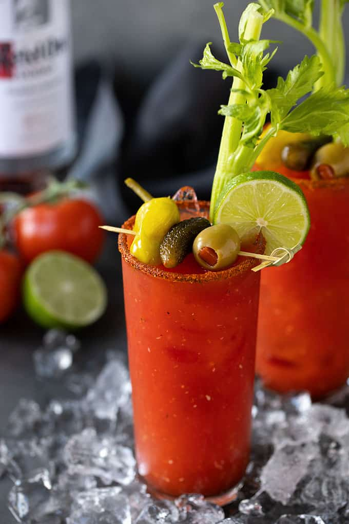 Two Bloody Mary Cocktails with garnishes. A bottle of vodka, fresh tomatoes and a lime are in the background.