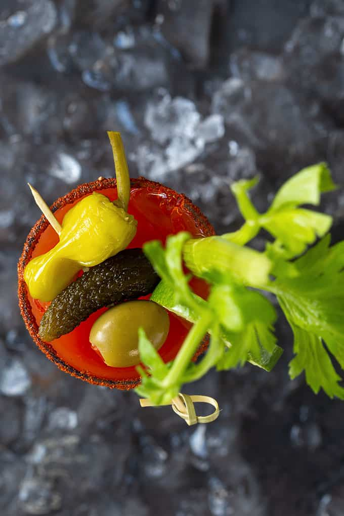 Overhead view of a Bloody Mary with a wooden skewer of olive, pickle and yellow pepper.