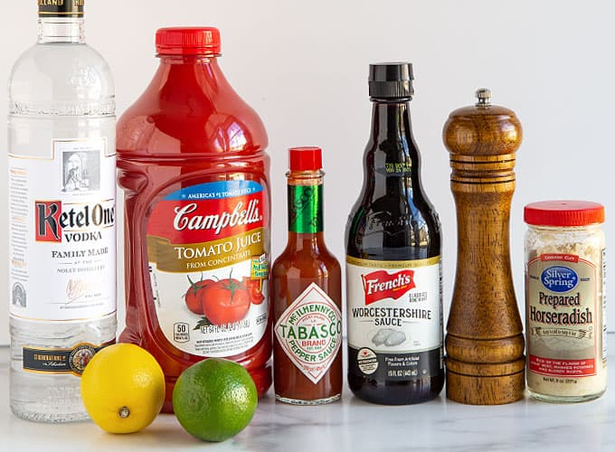 A bottle of vodka, tomato juice, Tabasco sauce, Worcestershire sauce, a pepper mill, prepared horseradish, a lemon and a lime