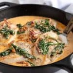 Chicken in a sun-dried tomato and spinach cream sauce in a cast iron skillet with a spatula under a piece of chicken