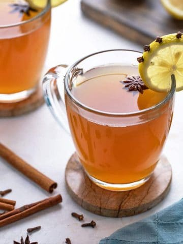 Hot toddy in a glass mug garnished with star anise and a clove-studded lemon wheel