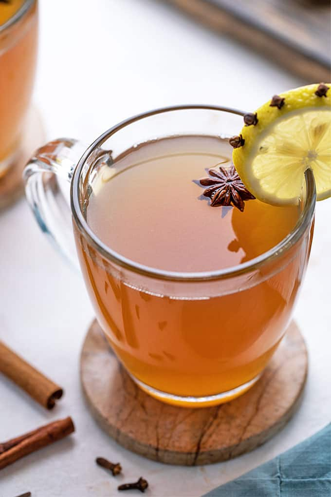 Hot toddy cocktail in a glass mug garnished with star anise and a clove-studded lemon wheel