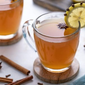 Hot toddy in a glass mug garnished with star anise and a clove-studded lemon wheel.