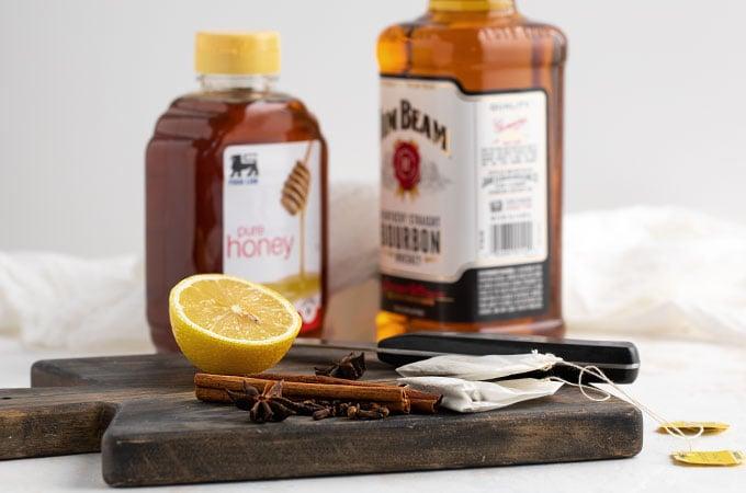 A fresh lemon for juicing, honey, bourbon, tea bags, cinnamon sticks and star anise