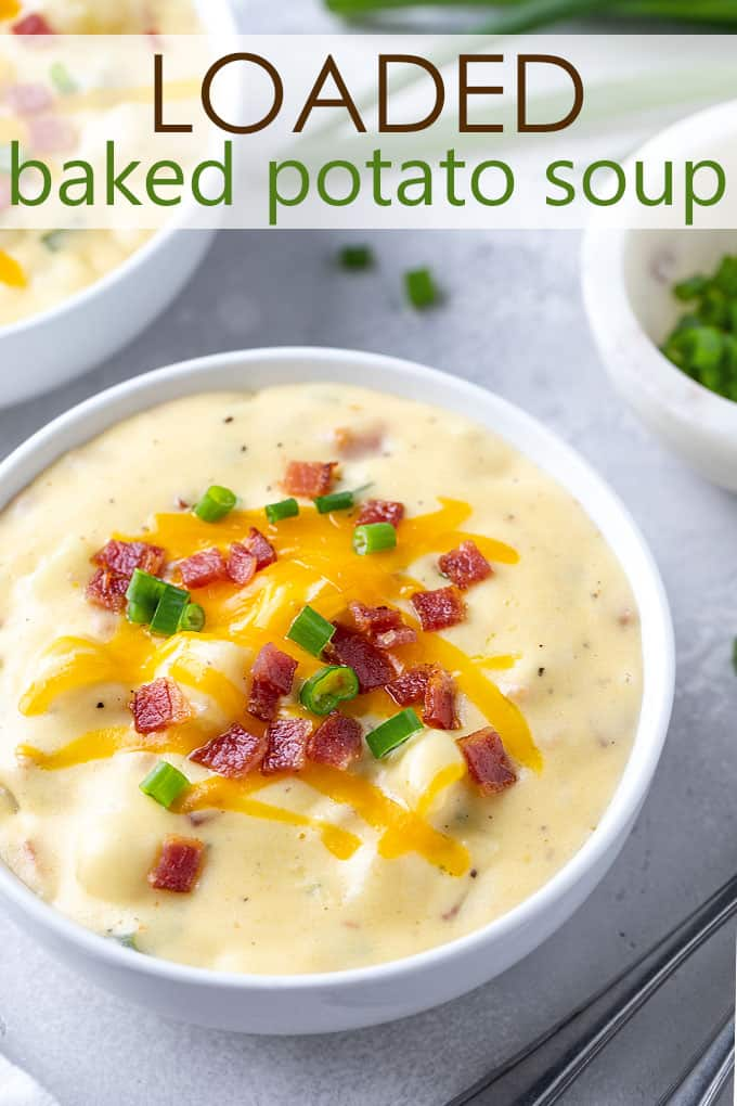 Baked potato soup in a white bowl garnished with bacon, green onions and cheese. Overlay text at top of image