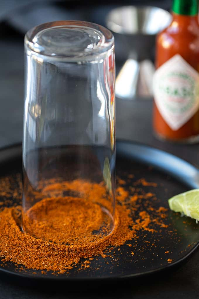 A glass turned upside-down being rimmed with old bay seasoning on a black plate with a lime wedge