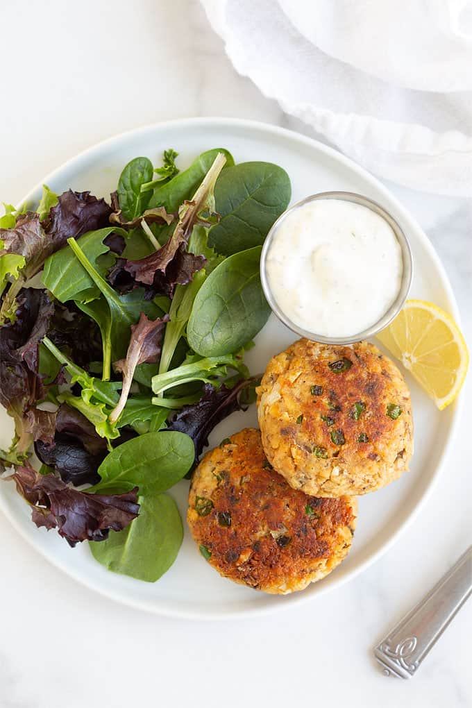 Overhead shot of 2 salmon cakes on a white plate with salad greens, tartar sauce and a lemon wedge