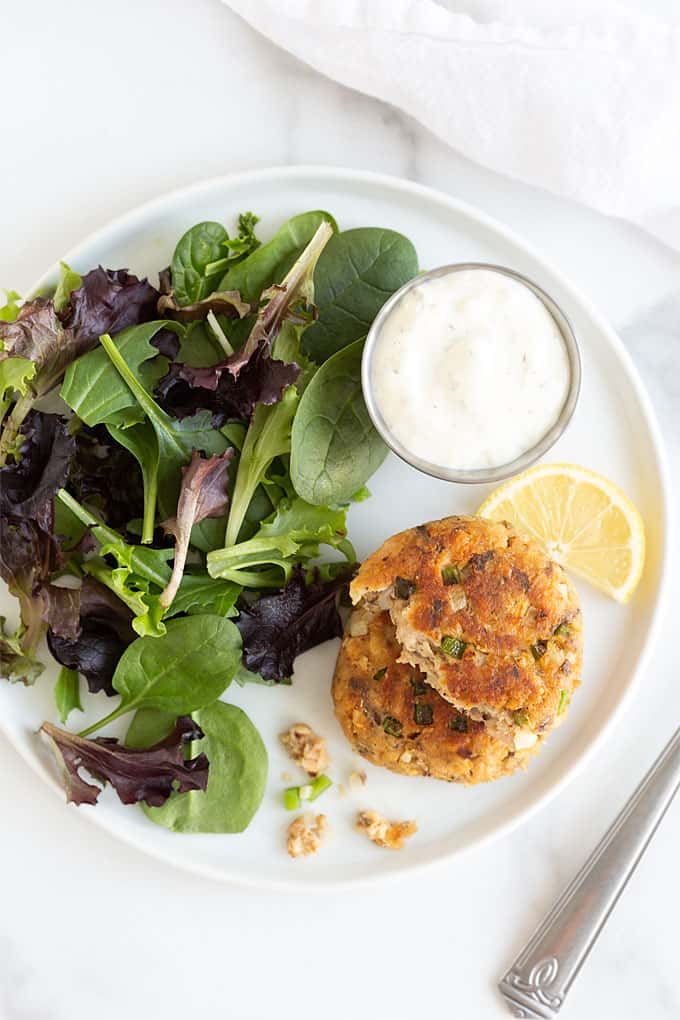 Overhead view of 2 stacked salmon patties on a white plate with salad greens, tartar sauce and a lemon wedge
