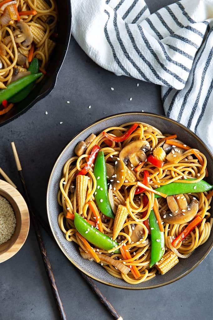 Overhead view of a bowl of vegetable lo mein beside chopsticks, a bowl of sesame seeds and a striped kitchen towel