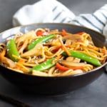 Vegetable Lo Mein in a blue bowl beside chopsticks. A striped kitchen towel is in the background.