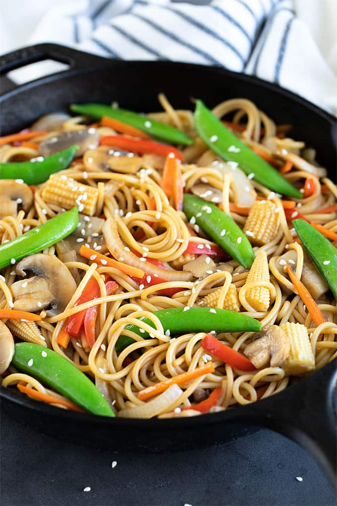 Vegetable lo mein sprinkled with sesame seeds in a cast iron skillet