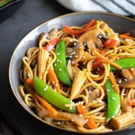 Vegetable lo mein in a blue bowl beside chopsticks. A striped kitchen towel and skillet is in the background.