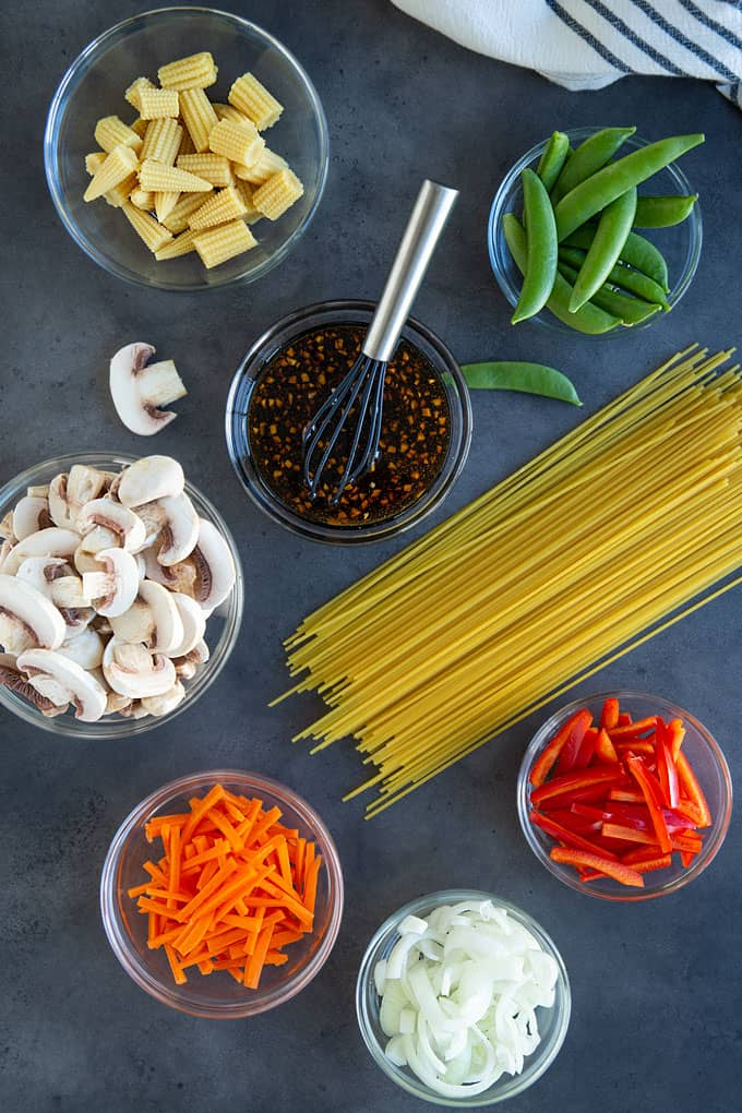 Overhead view of a bowl of lo mein sauce with a whisk, bowls of sliced vegetables and uncooked spaghetti noodles