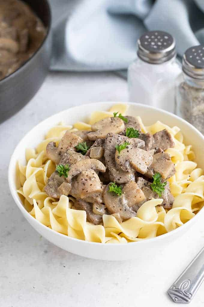 Beef stroganoff over egg noodles in a white bowl. Salt and pepper shakers and a skillet is in the background.