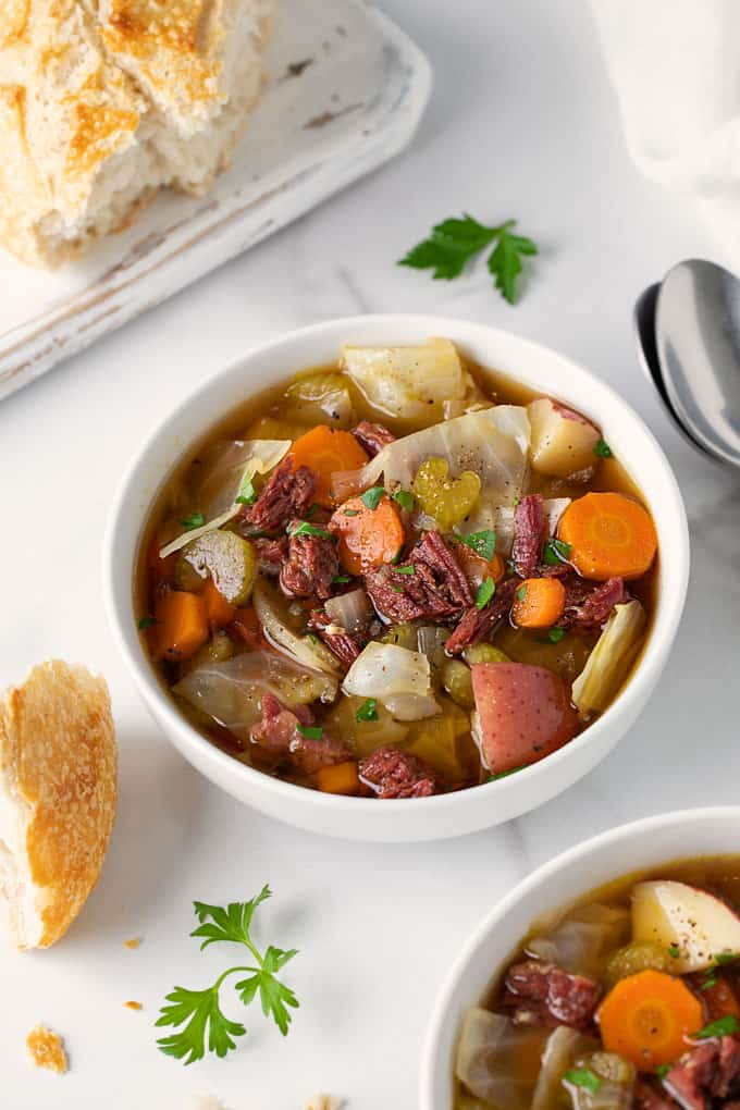Overhead view of corned beef and cabbage soup in a white bowl on a marble background beside a piece of sourdough bread