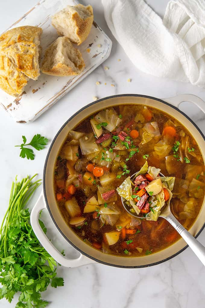 Overhead view of corned beef and cabbage soup in a white dutch oven with a ladle beside sourdough bread and a bunch of parsley