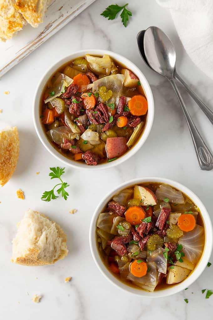Overhead view of 2 bowls of corned beef and cabbage soup beside 2 spoons and sourdough bread
