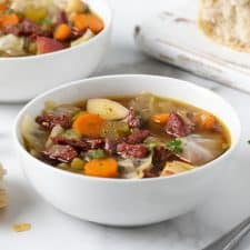 Corned beef and cabbage soup in 2 white bowls with sourdough bread in the background