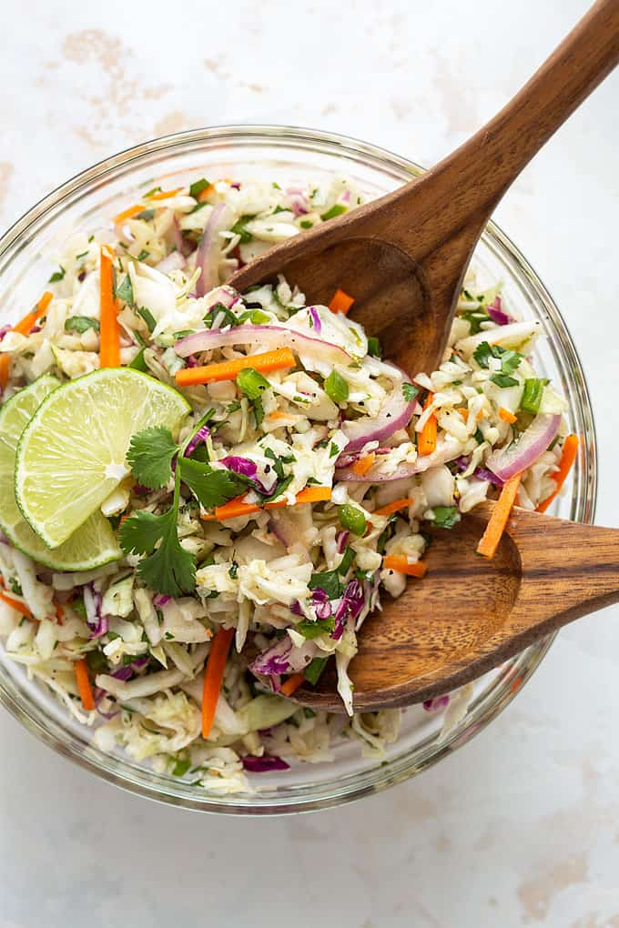 Overhead view of a bowl of Mexican coleslaw with wooden servers.