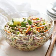 Mexican coleslaw in a glass bowl beside 2 wooden servers. A white napkin and stack of plates is in background.