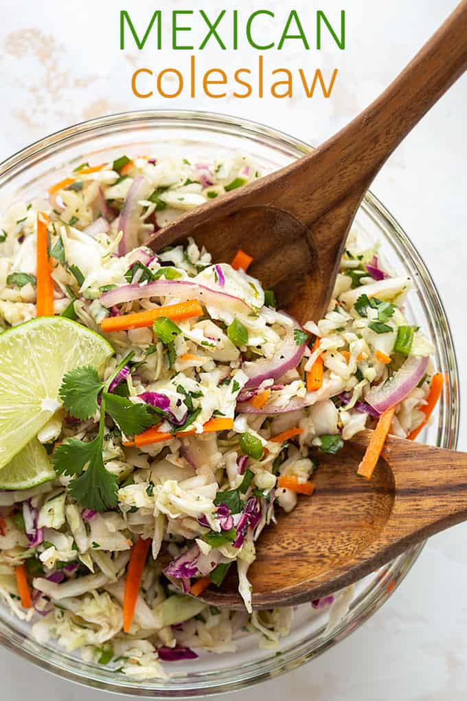 Overhead view of Mexican coleslaw in a glass bowl with 2 wooden servers. Overlay text at top of image.