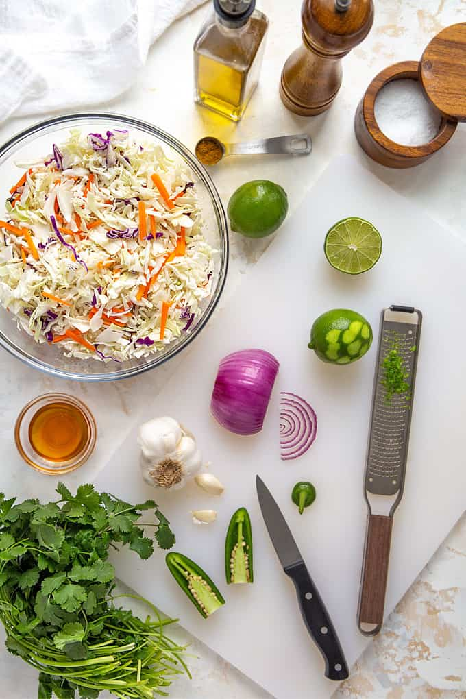 Overhead view of a bowl of shredded cabbage and a cutting board with limes, cilantro, garlic, jalapeno peppers and onion